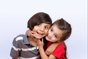 Two kids hugging each other.