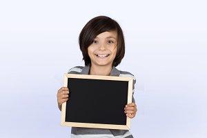 Little boy holding chalkboard.