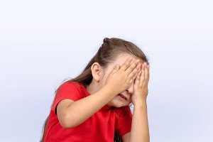 Little girl covering face and scare.