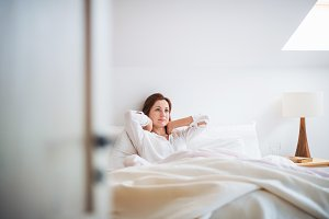 A young woman sitting in bed indoors
