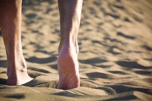 young man walking down a dune