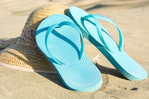 summer shoes and hat on sand