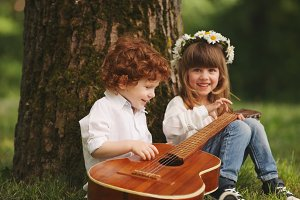 boy and girl playing guitar in