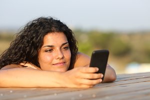 Relaxed girl watching social media in smart phone.jpg