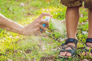dad and son use mosquito spray