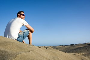 man sitting on a dune