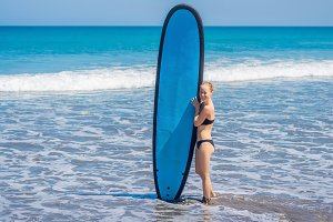 Surfer girl on the sandy beach
