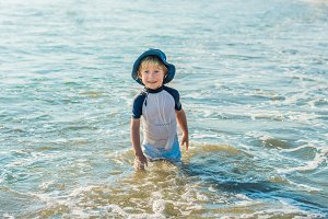 happy little boy running on sand