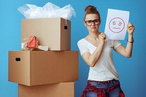 woman near cardboard box showing a s