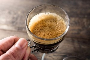 Hand holding a coffee glass