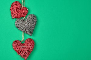 three wicker hearts hang on a rope
