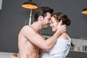 adult man and woman smiling and embr