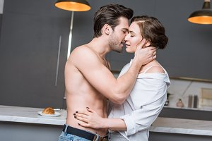 adult couple kissing at kitchen with