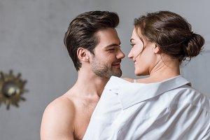 adult man gently taking off shirt fr