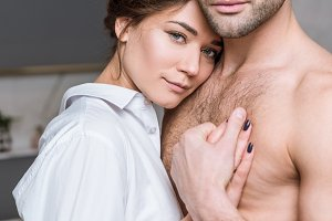 Adult tender couple embracing at hom