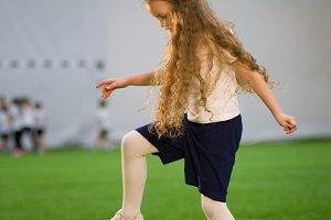 A little girl playing football