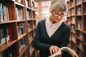 Senior woman looking at a book stand