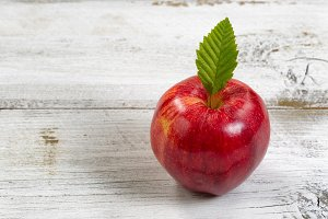 Whole Red Apple on white wood