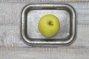 Golden apple on old silver tray