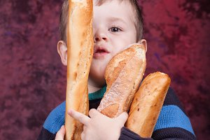 Cute kid holding French bread