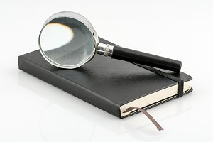 Black magnifying glass and book