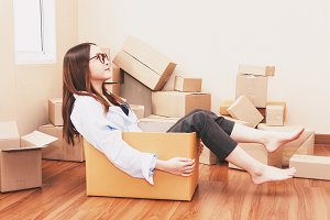 Young woman sitting in a cardboard