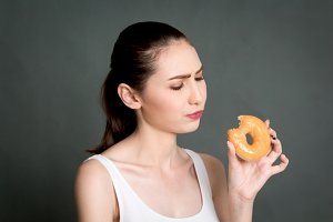 Woman holding donut on gray