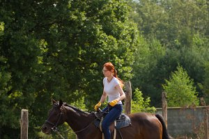 A redhead woman riding a horse on a
