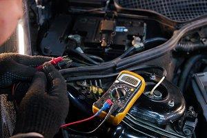 Car service. Mechanic man checks the