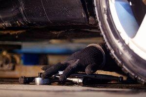 Car service. Mechanic man reaching