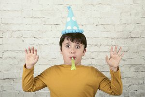 surprised child wearing a party hat