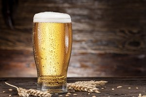 Frosted glass of beer on the wooden