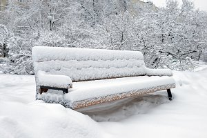 Bench in park filled up with a snow