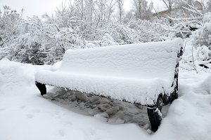 Bench filled up with a snow
