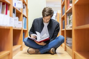 man in library reading book sitting