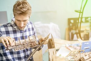 young carpenter assemble wooden toys
