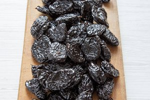 Dry prunes on rustic wooden board