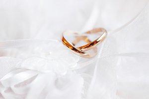 Golden wedding rings, white silk