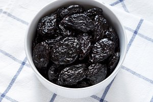 Dry prunes in a bowl, high angle