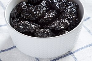 Full bowl of dry prunes, side view.