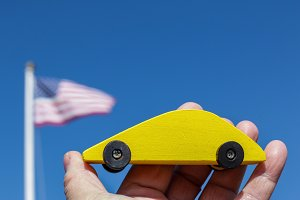 Yellow wooden car holding in hand