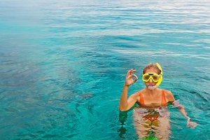 Young woman in snorkeling mask showi