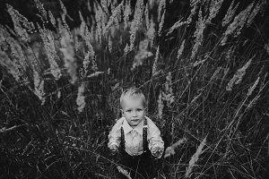 sad little boy portrait in high gras