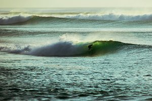 Surfer rides in the barrel