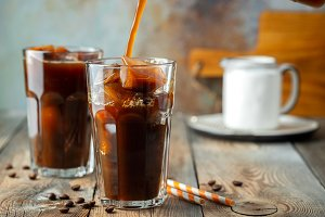 Ice coffee in a tall glass with crea
