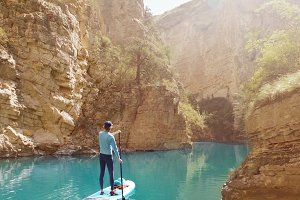 Man on SUP board into a canyon.