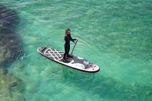 Woman on SUP board in a blue sea