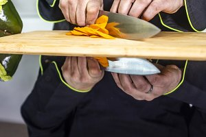 Chef cutting carrot on a wooden boar