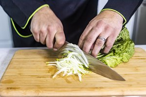Chef cutting cabbage  on a wooden bo
