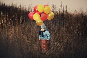 little boy in basket with balloons